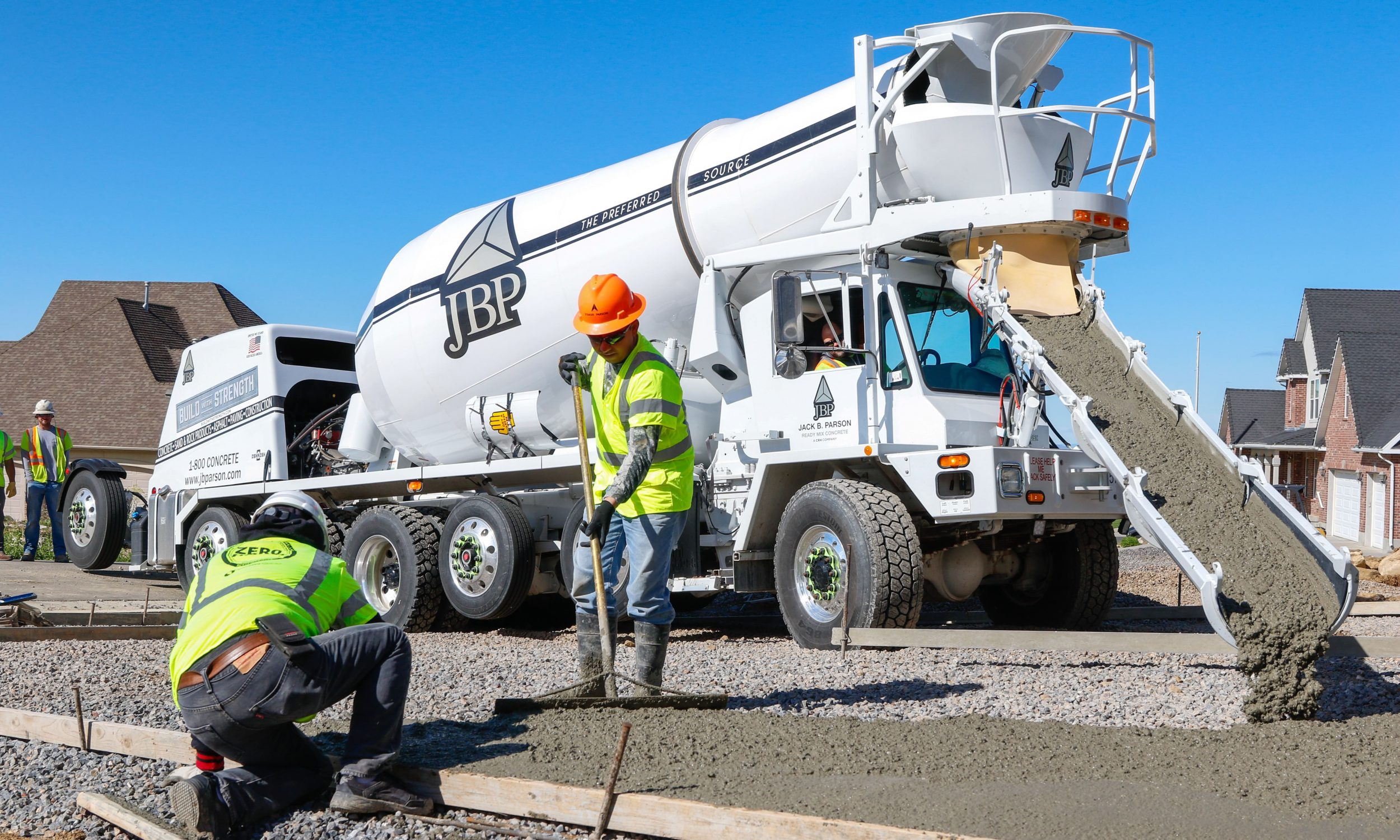 Image of Jack B Parson concrete mixer with crew finishing concrete at new subdivision in North Ogden UT