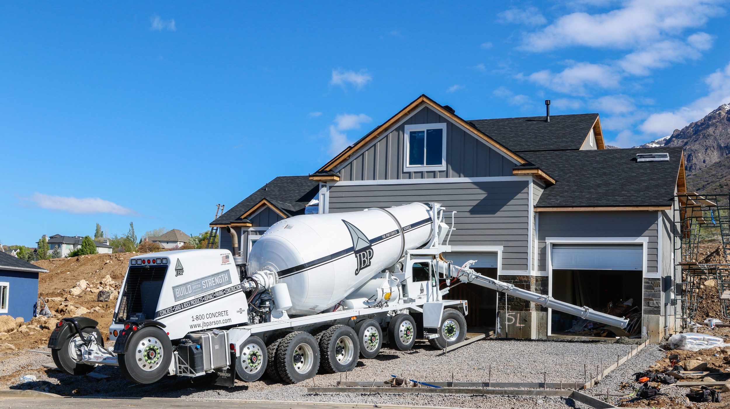 Image of a Staker Parson concrete truck getting ready to dispense concrete for a new driveway at a new home in North Ogden, UT