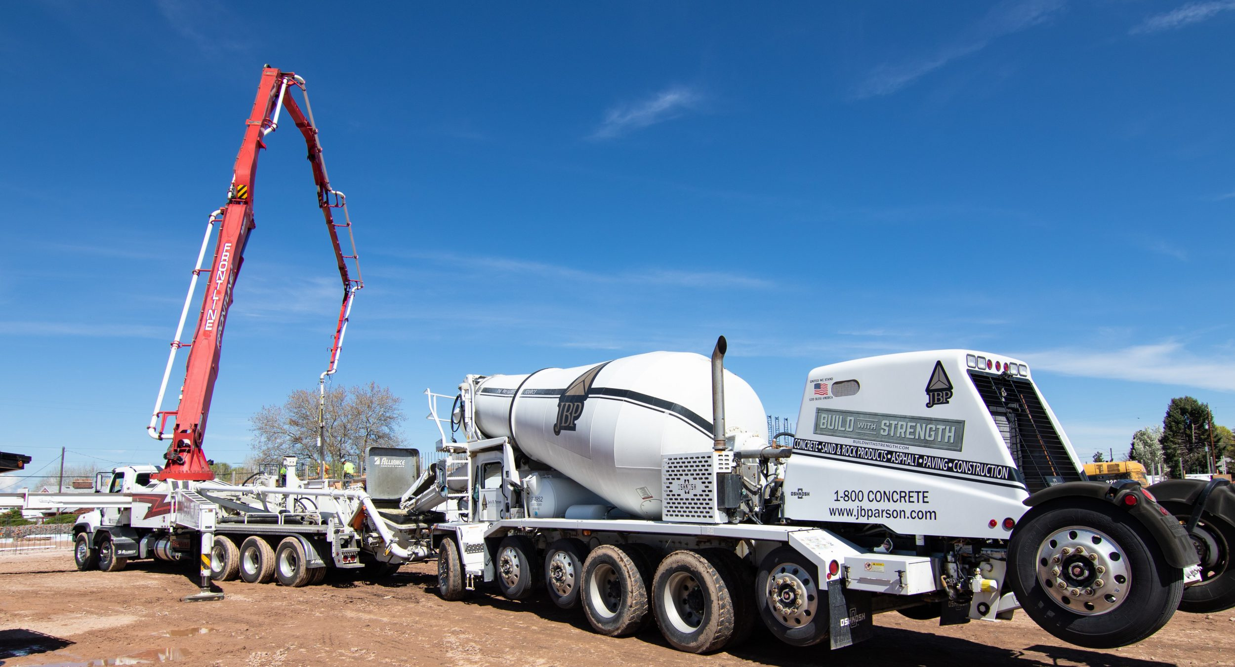 The image is a picture of a Staker Parson concrete mixer at the new Roy High School- 1-800-CONCRETE